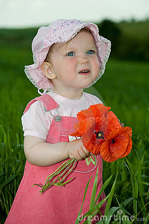 Free Child With Red Flower Amongst Green Grass Royalty Free Stock Images - 5501099