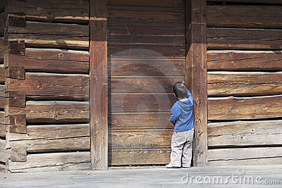 Child at wooden barn door
