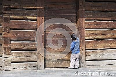 Child at wooden barn door