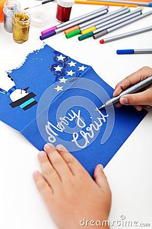 Child writing christmas greeting card