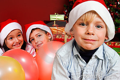 Children with ballons by Christmas tree