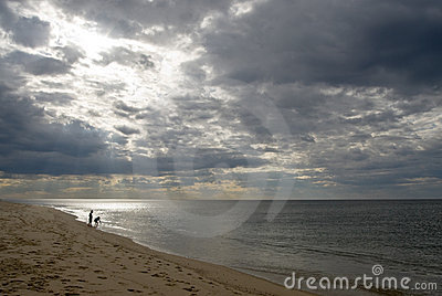 Children on beach, dramatic sky, stormy clouds