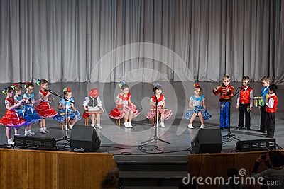 Children in beautiful costume performs on stage