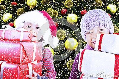 Children bring christmas gifts under tree