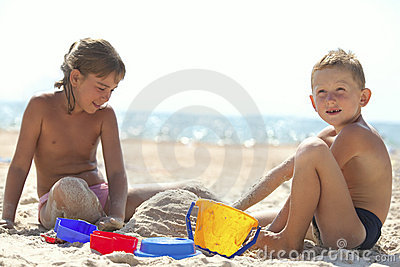 Children building sand castle on beach