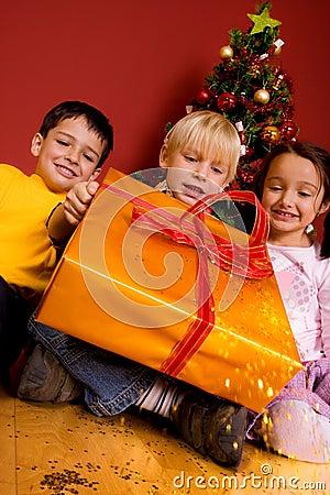 Children carrying christmas gift