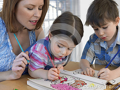 Children Coloring Book While Mother Assisting Them Stock Photo