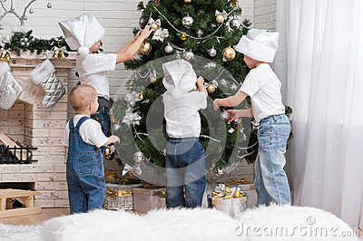 Children decorate a Christmas tree toys