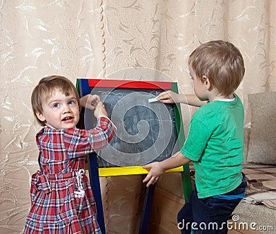 Children draws on  blackboard with chalk
