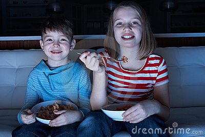 Children Enjoying Meal Whilst Watching TV