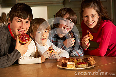 Children Enjoying Plate Of Cakes In Kitchen
