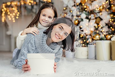 Children, family and celebration concept. Adorable female in knitted sweater holds white present box and small kid stands behind Stock Photo