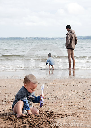 Children and father on the beach