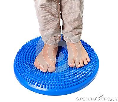 Children feet on the massage pillow