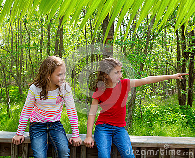 Children friends playing pointing finger to jungle park