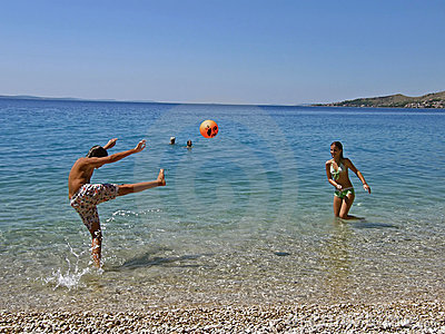 Children in fun wit ball on sea