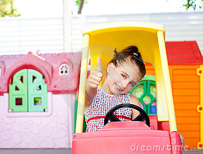 Children girl driving a toy car with ok gesture