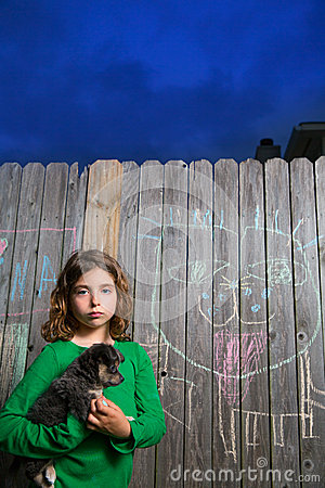 Children girl holding puppy dog on backyard wood fence