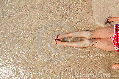 Children girl legs in beach sand shore