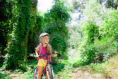 Children girl riding bicycle in forest smiling
