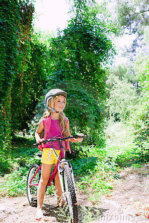 Children girl riding bicycle outdoor in forest