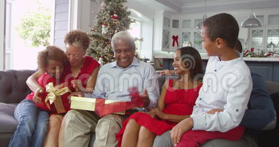 Children giving grandparents Christmas gifts at home - they shake packages and try to guess what's inside. Children Give Christmas Gift To Grandparents Shot On stock footage