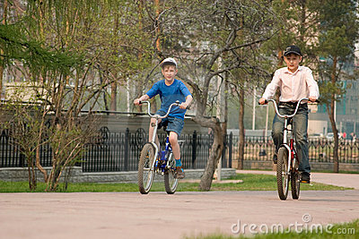 Children go for a drive on bicycles on park.