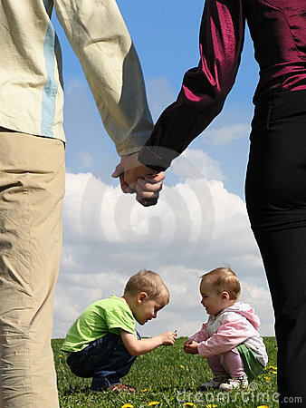 Children on grass and parents holding hands