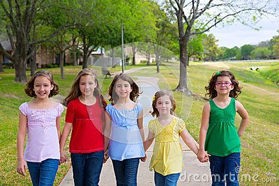 Children group of sisters girls and friends walking in park