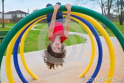 Children kid girl upside down on a park ring