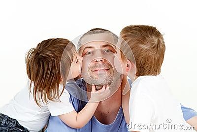 Children kissing dad