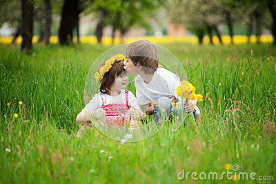 Children kissing in meadow