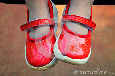 Children legs in red shoes