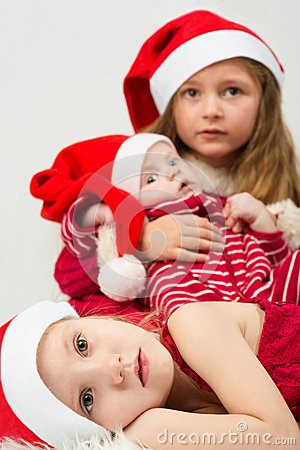 Children lie on fur in the hats of Santa Claus