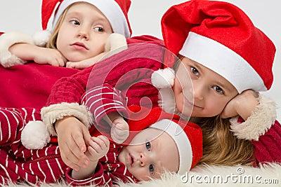 Children lie in the hats of Santa Claus