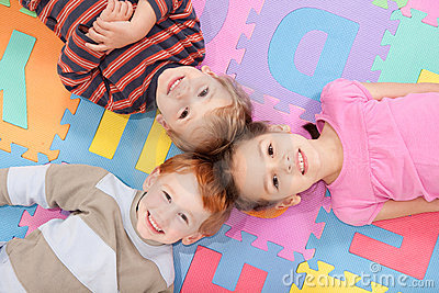 Children lying on backs on fun kids alphabet mat