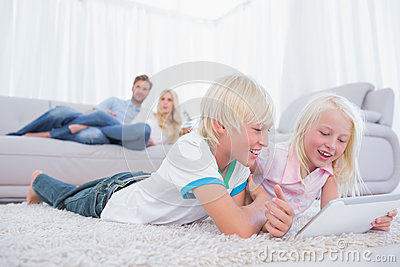Children lying on the carpet using digital tablet