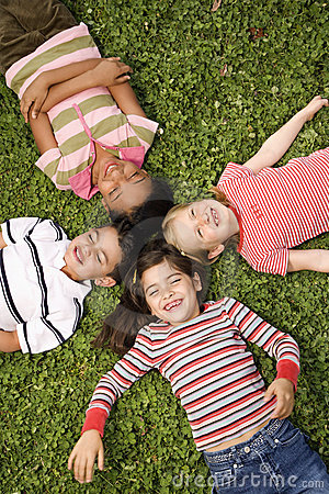 Free Children Lying In Clover With Heads Together Royalty Free Stock Image - 12528906