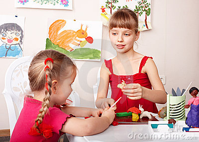 Children molding  plasticine in playroom.