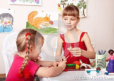 Children molding  plasticine in playroom.