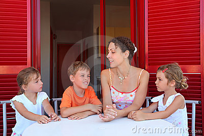 Children and mother sit on verandah round table