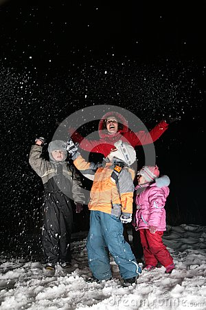 Children and mother throw snow in night