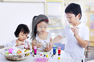 Children painting easter eggs in art class