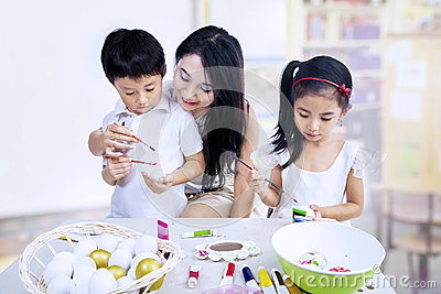 Children painting eggs in class