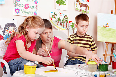 Children painting with young woman.