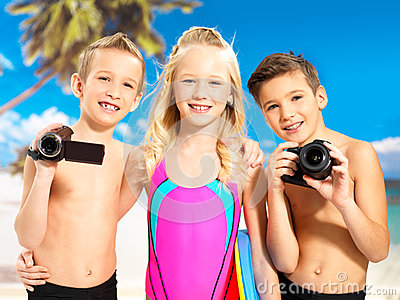 Children with photo and video camera at beach.