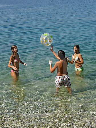 Children play with a ball in sea