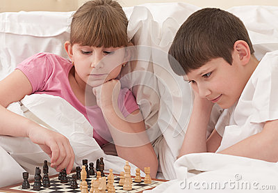 Children play chess in a bed