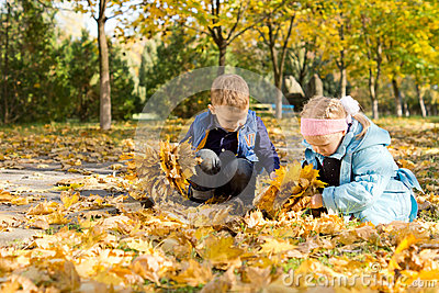 Children playing in a carpet of autumn leaves