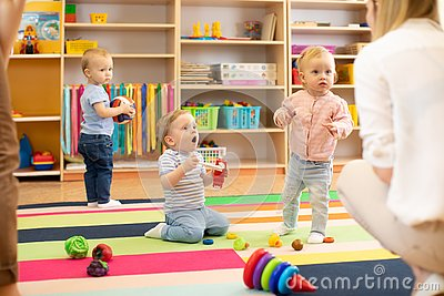Nursery babies play on floor with carers or mothers in day care centre Stock Photo